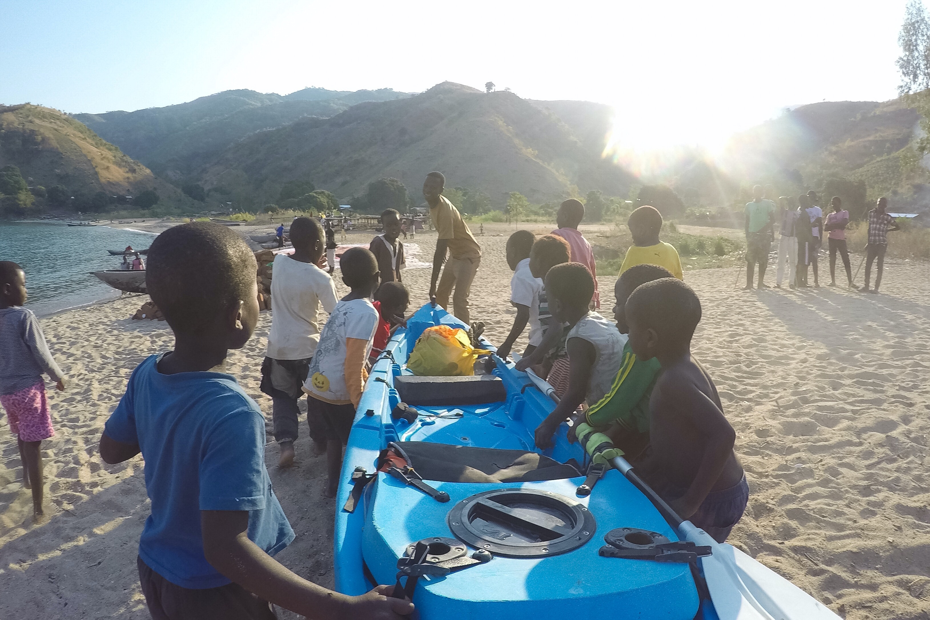 Village kids helping Rigby move his kayak, toward the end of his journey.
