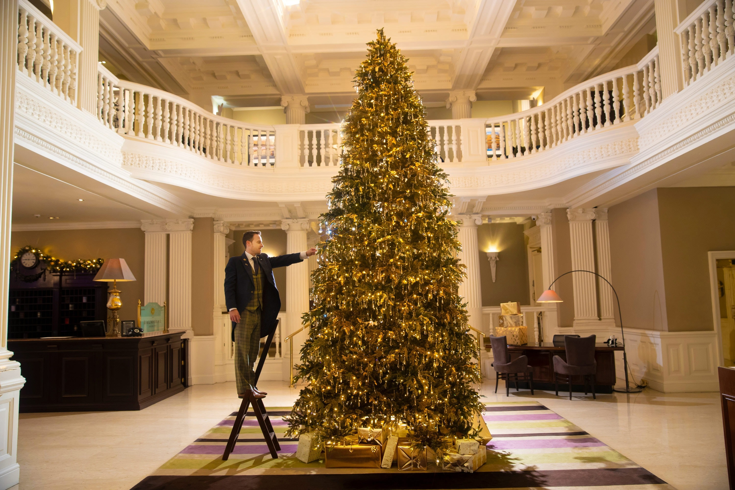A concierge puts some finishing touches on the tree at The Balmoral.