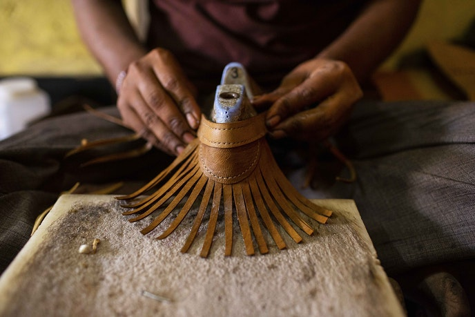 As the shoes are being assembled, laces on the upper parts are threaded through holes in the soles and then knotted.