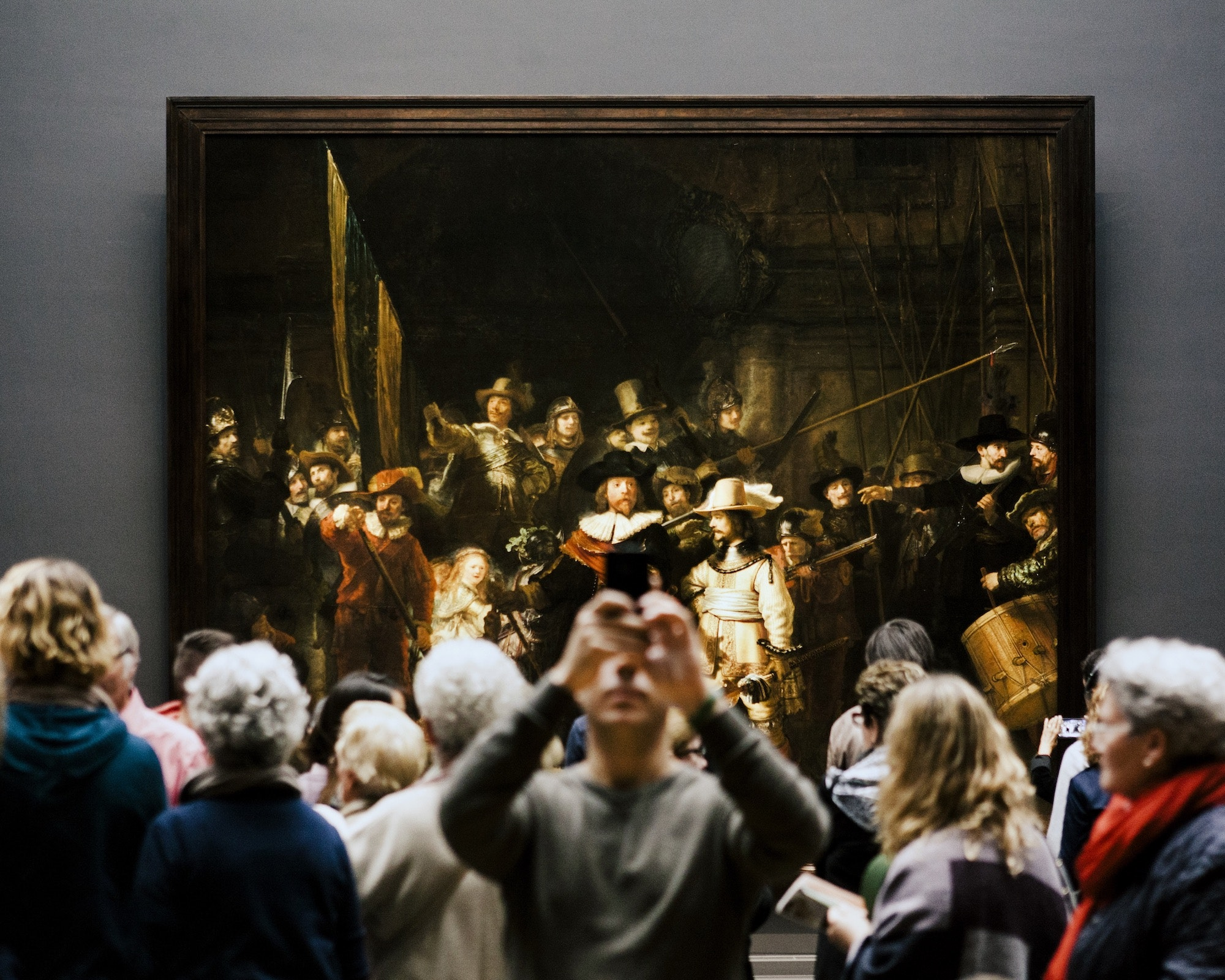 """Onlookers gather in front of Rembrandt's """"The Night Watch"""" in Amsterdam's Rijksmuseum."""