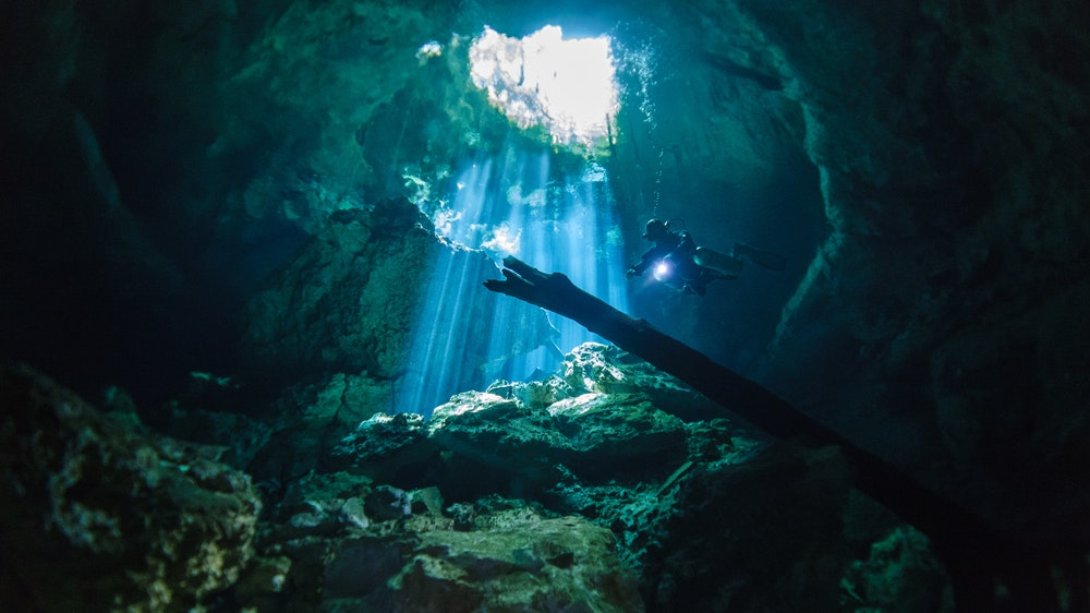 A cave diver wearing sidemount air tanks explores Cenote Tajma-Ha in Mexico