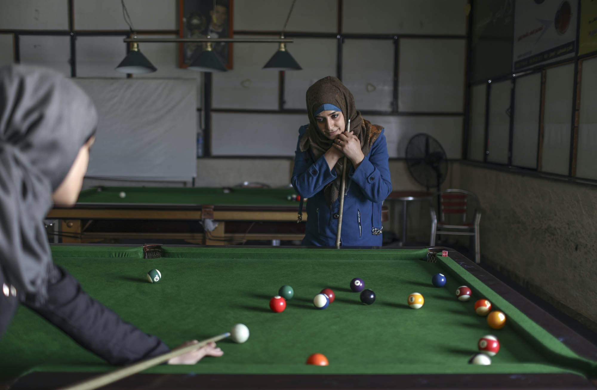 Palestinian girls play pool at a café in Gaza.