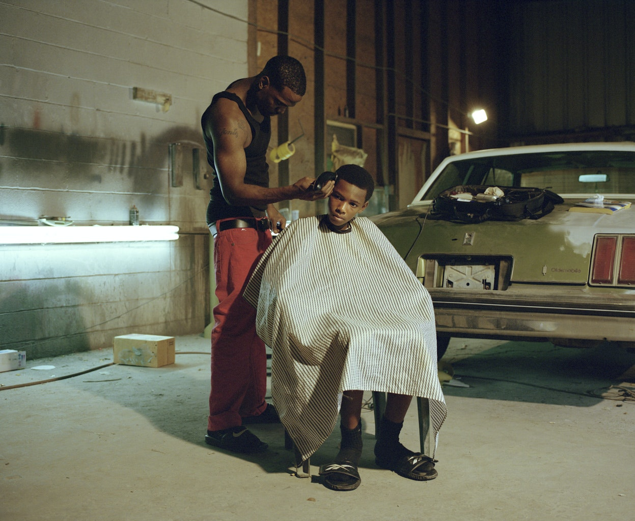 A man gives his brother a haircut in the garage where they work in Baton Rouge, Louisiana.