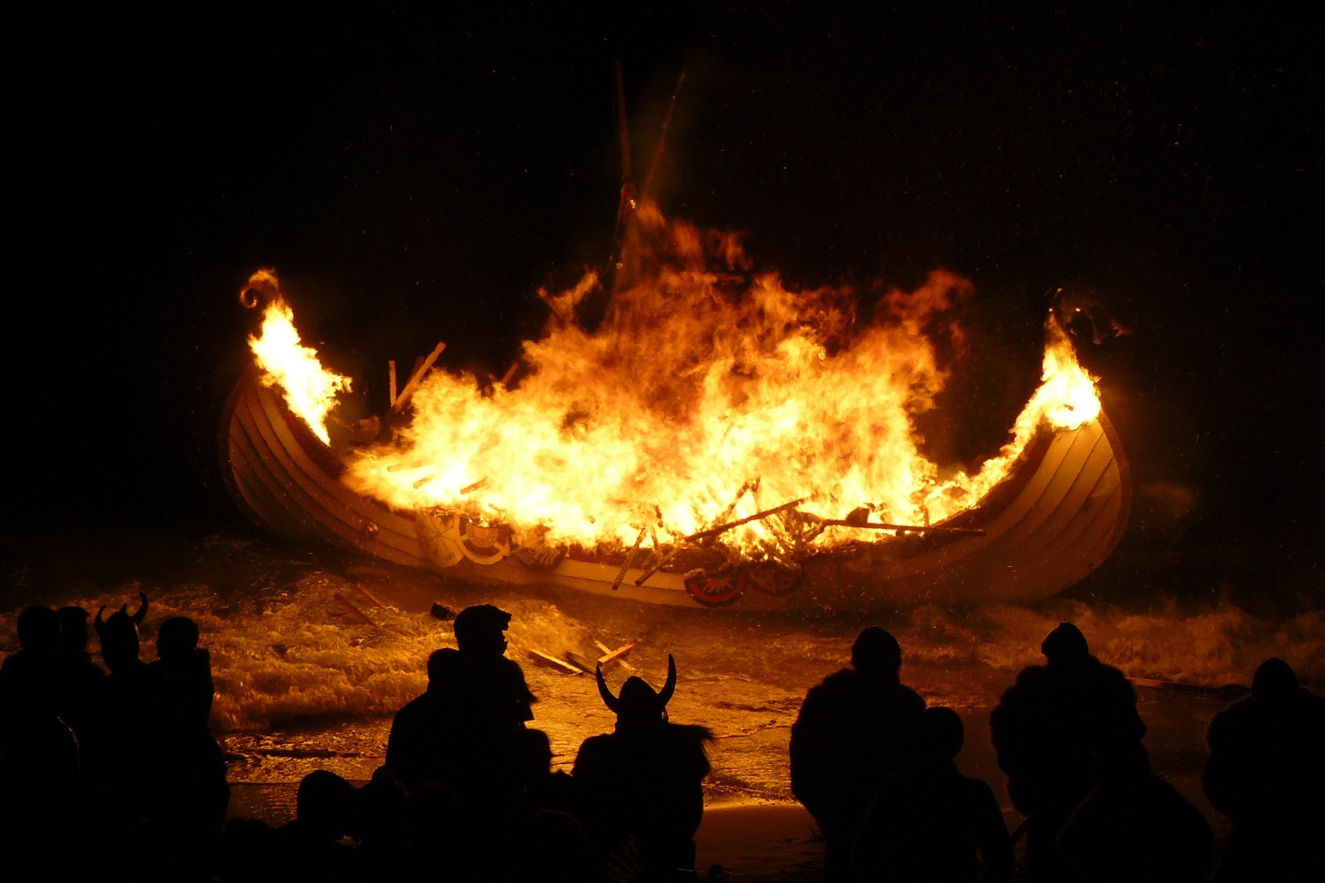 The torch-lit procession culminates in the burning of a life-size Viking ship replica.