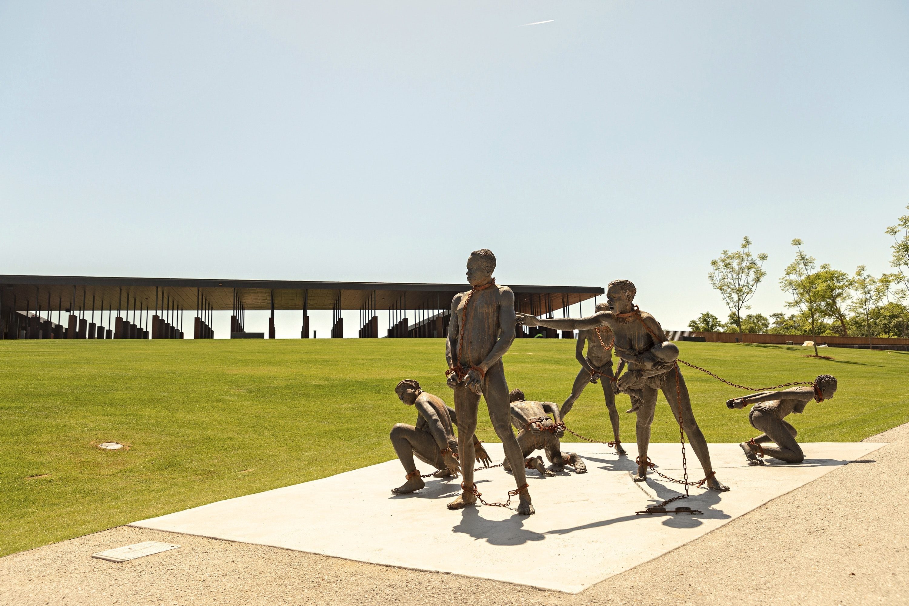 Seven sculpted figures by Ghanaian artist Kwame Akoto-Bamfo confront visitors at the memorial entrance.