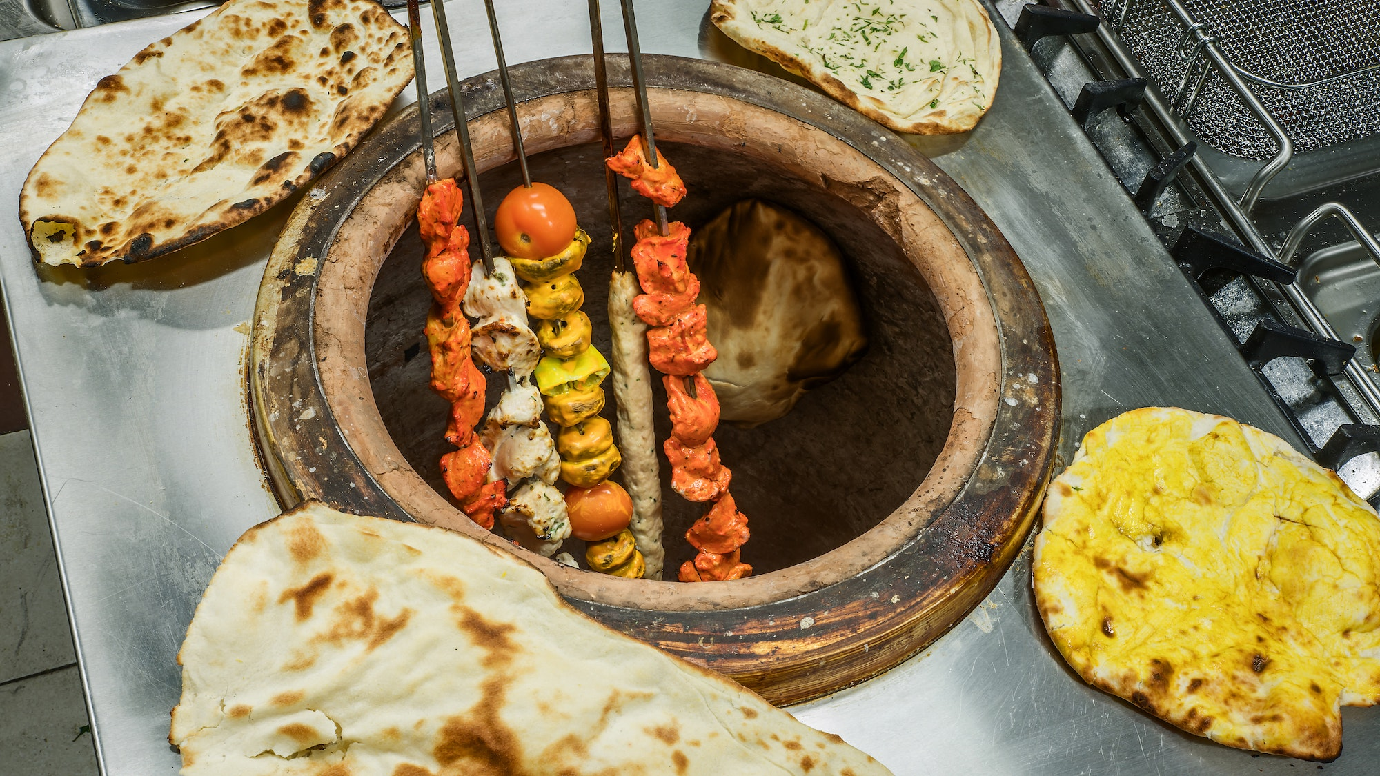 Skewered meat sits directly on the flame in a tandoor oven.