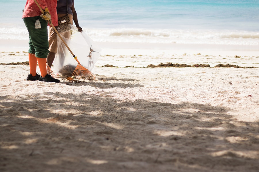 One easy way to give back while traveling: Spend a few moments picking up trash littering your favorite beach.