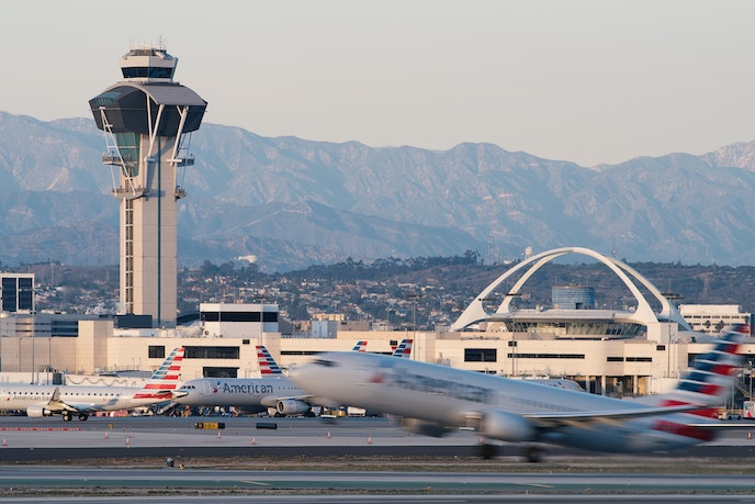 The Theme Building at Los Angeles International Airport is situated between a runway and the San Gabriel mountains.