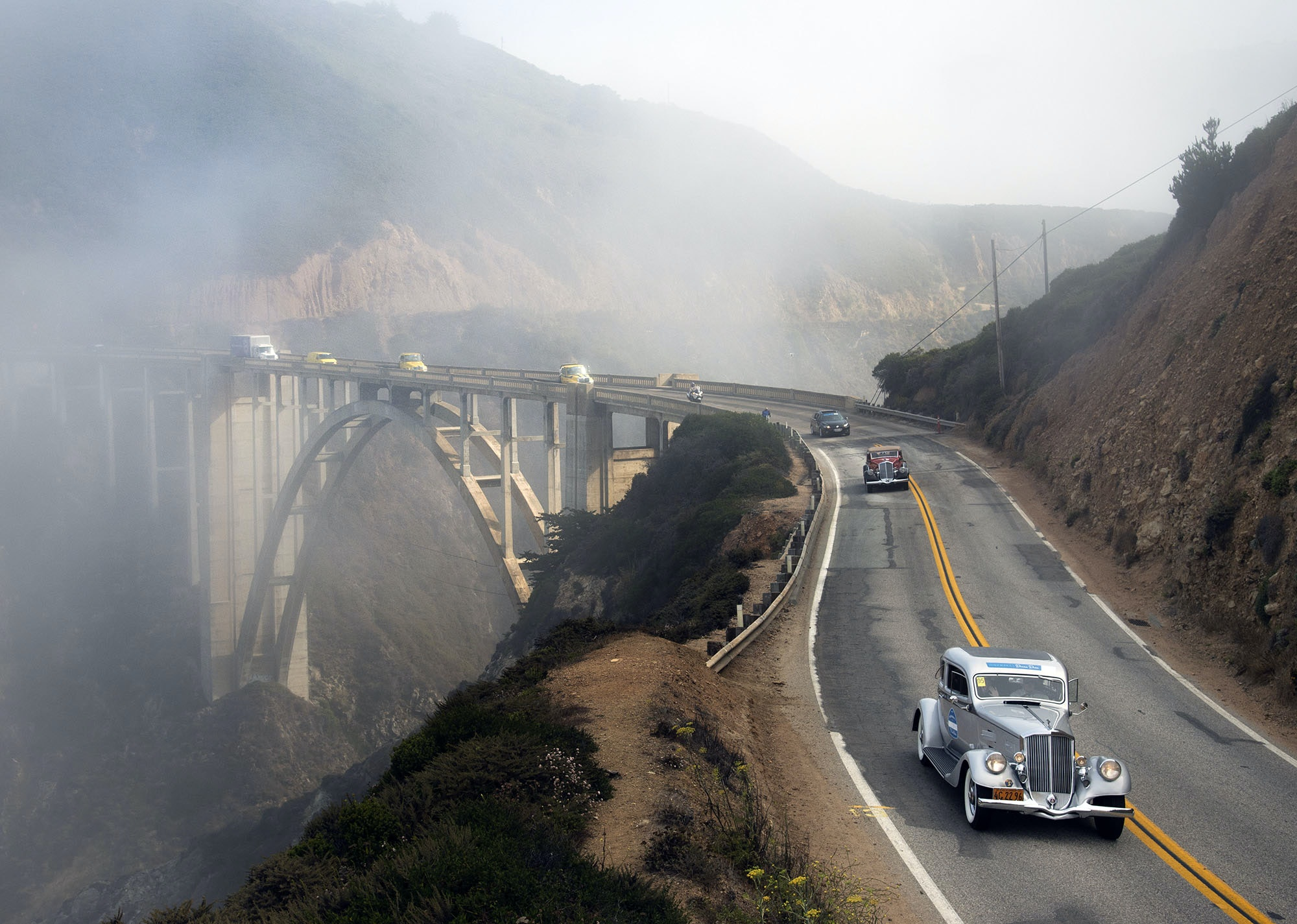 The cars process across Bixby Bridge.