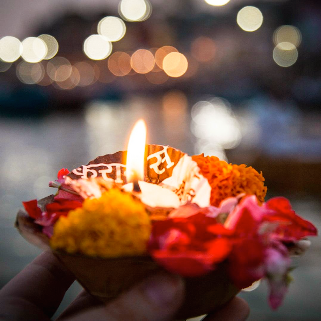 Individual candle decorated with marigolds and bougainvillea.