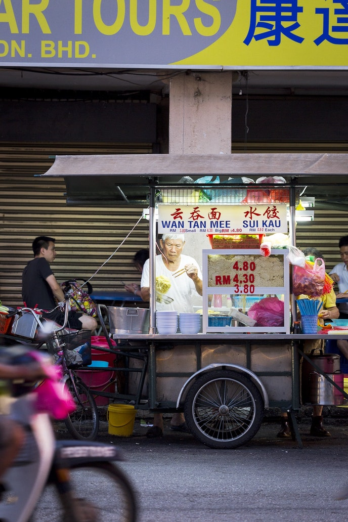 A noodle vendor works on Penang's busy Chulia Street.