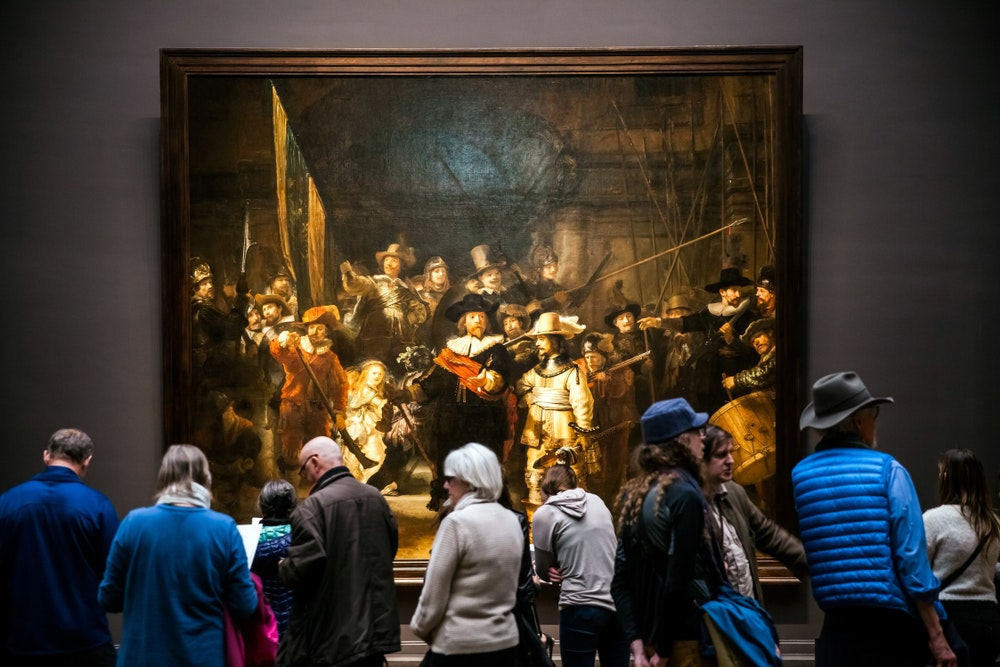 """Visitors to the Rijksmuseum look at """"The Night Watch"""" by Rembrandt."""