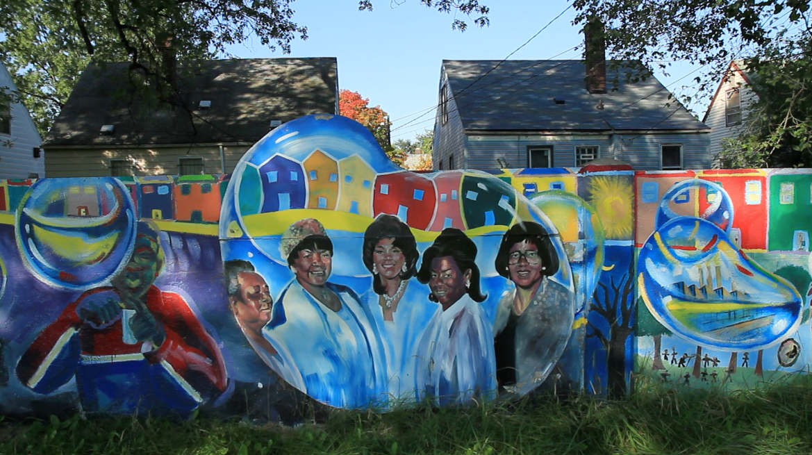 Detroit's Eight Mile Wall now features uplifting imagery of children blowing bubbles, colorful houses, and inspirational figures.