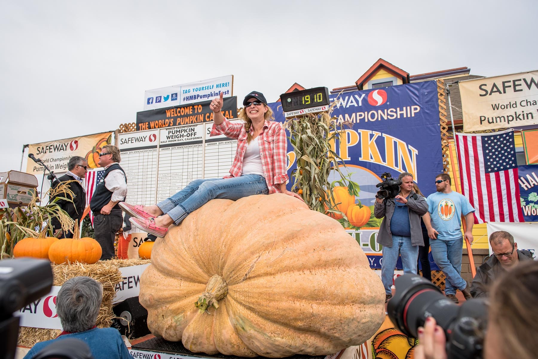 2016 Pumpkin Weigh-Off Winner Cindy Tobeck sits atop her prized pumpkin in Half Moon Bay.