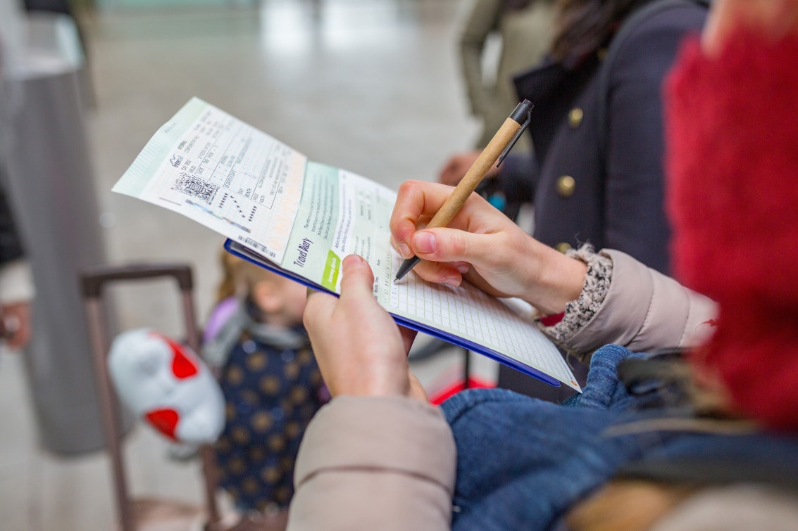 A traveler fills out her Eurail Pass to record which trains she took that day.