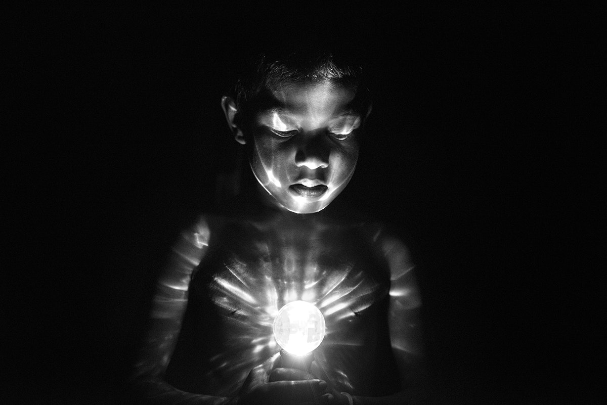 """A child with achromatopsia plays with a disco flashlight. He told De Wilde he sees """"colors"""" when he looks at it."""