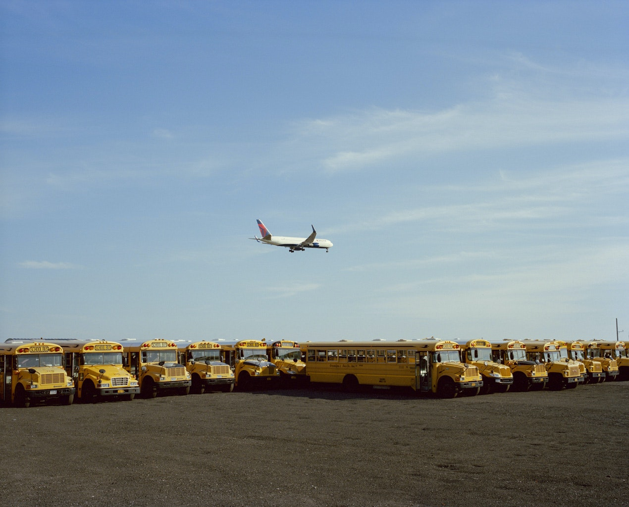 A plane leaving John F. Kennedy International Airport flies above a school bus parking lot on Long Island, New York.