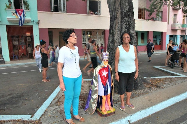 Two women stand with a life-sized statue of Saint Lazarus on the side of the avenue where the papal motorcade passed.