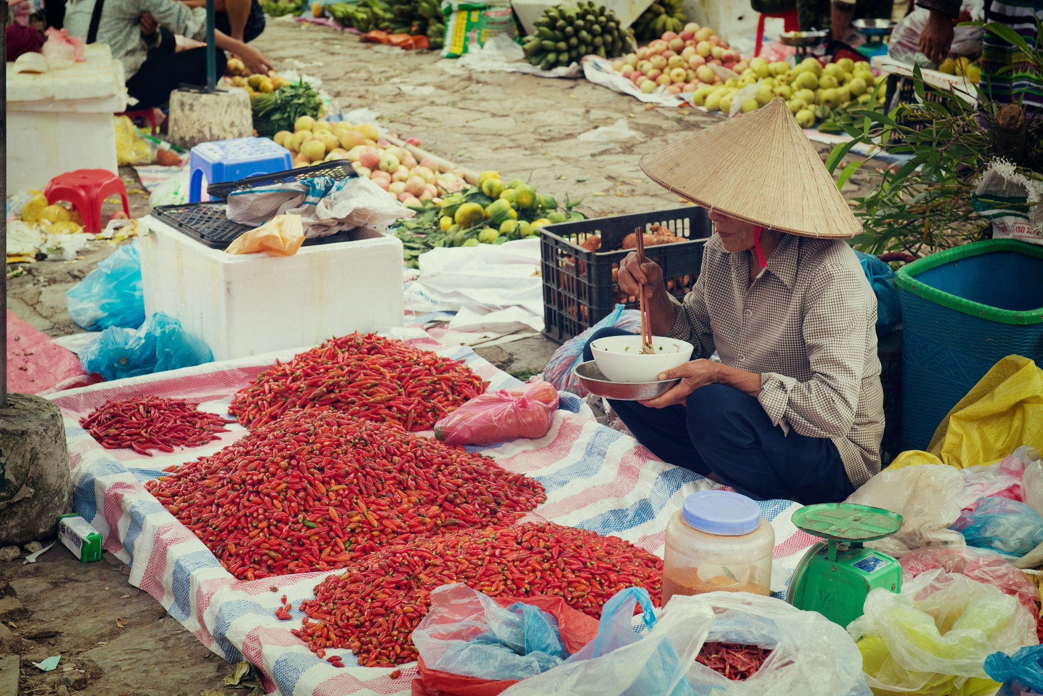 A pepper vendor eats lunch while peddling her wares in Vietnam.