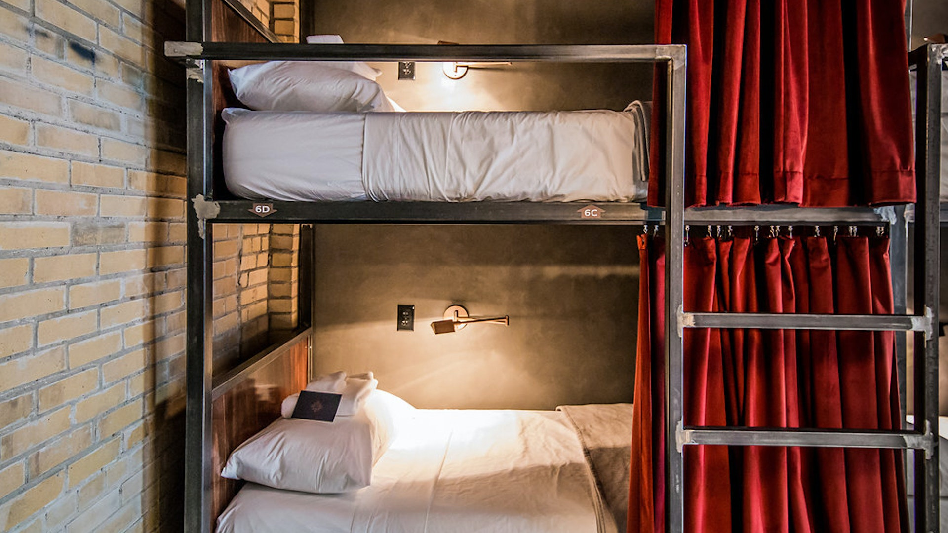 Bunk-style beds include privacy curtains, power outlets, and a reading lamp.