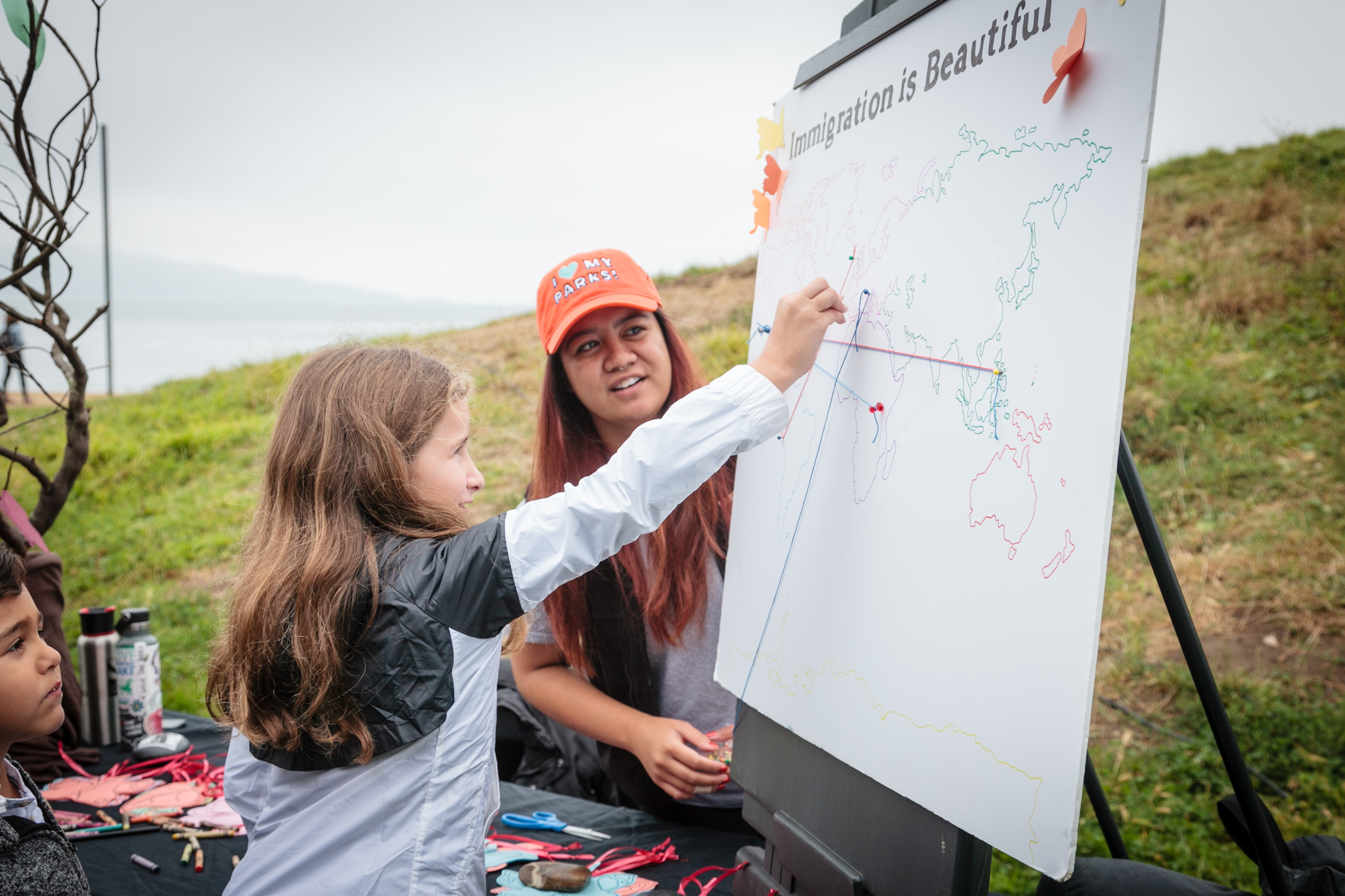 A volunteer from the Parks Conservancy looks on while a child marks her family's country of origin.