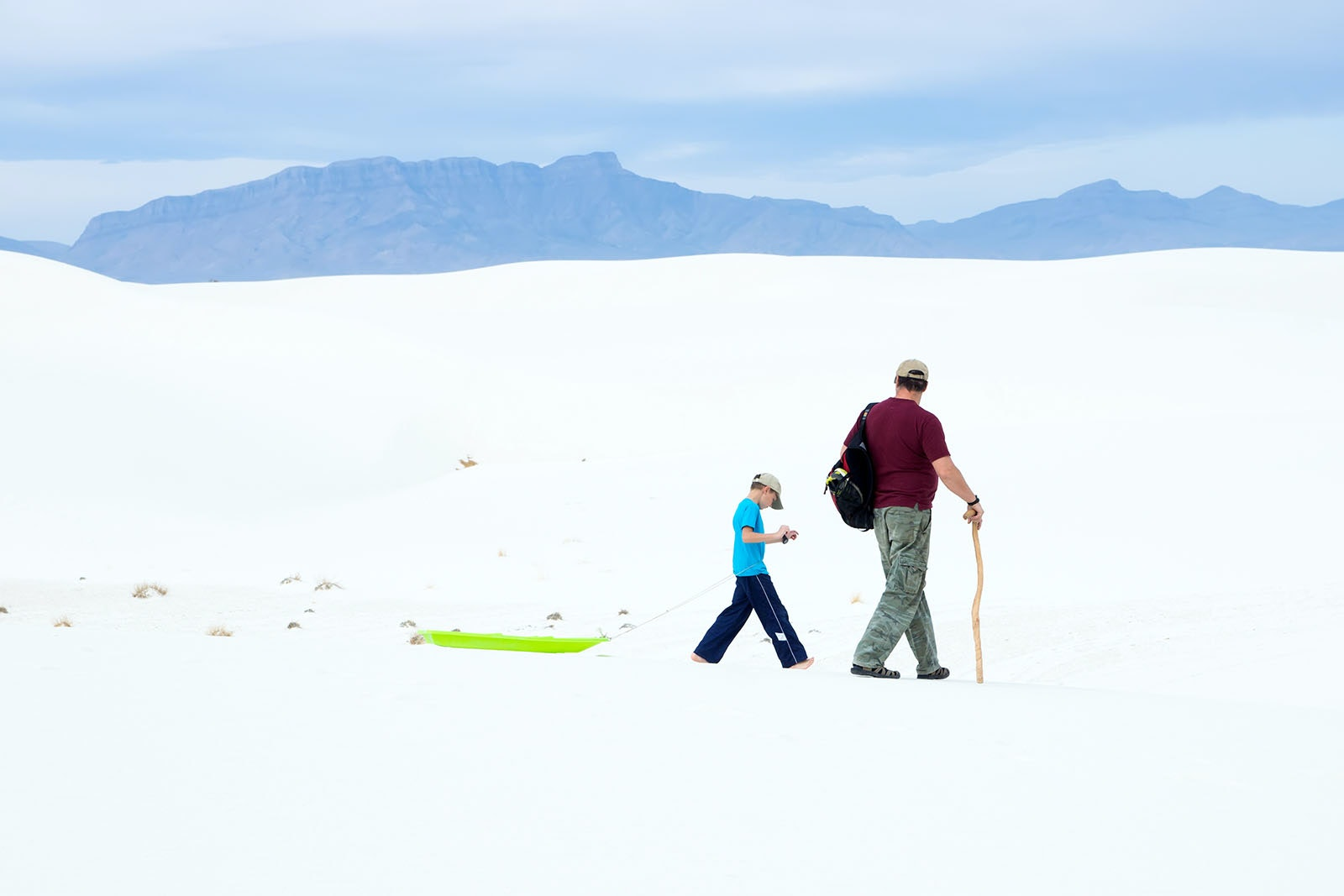 A father and son walk across White Sands National Monument with a sled.