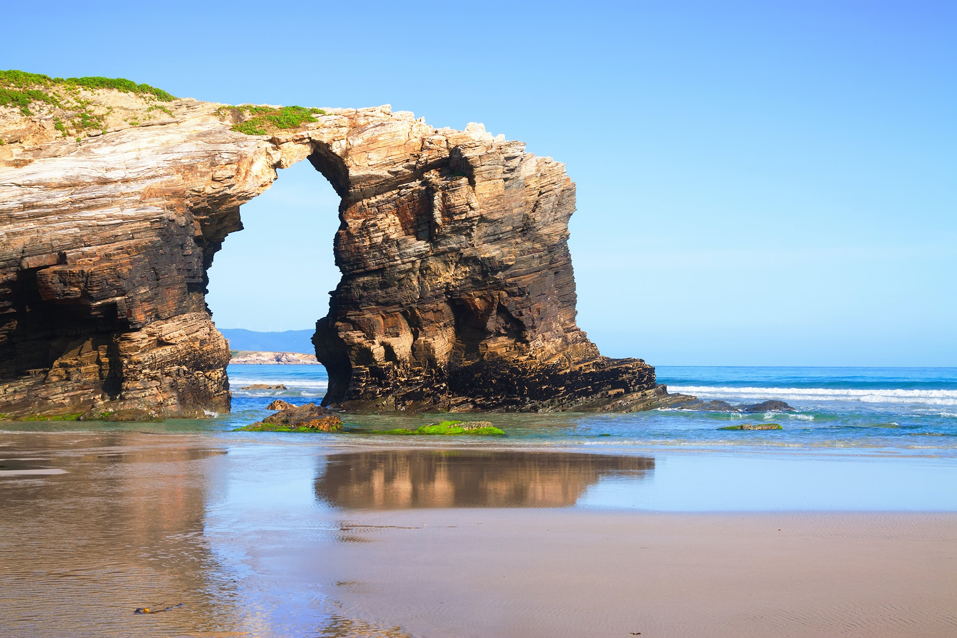 The seascape at Spain's Praia de Augas Santas is marked by spectacular nature-carved sculptures, set atop golden sands.