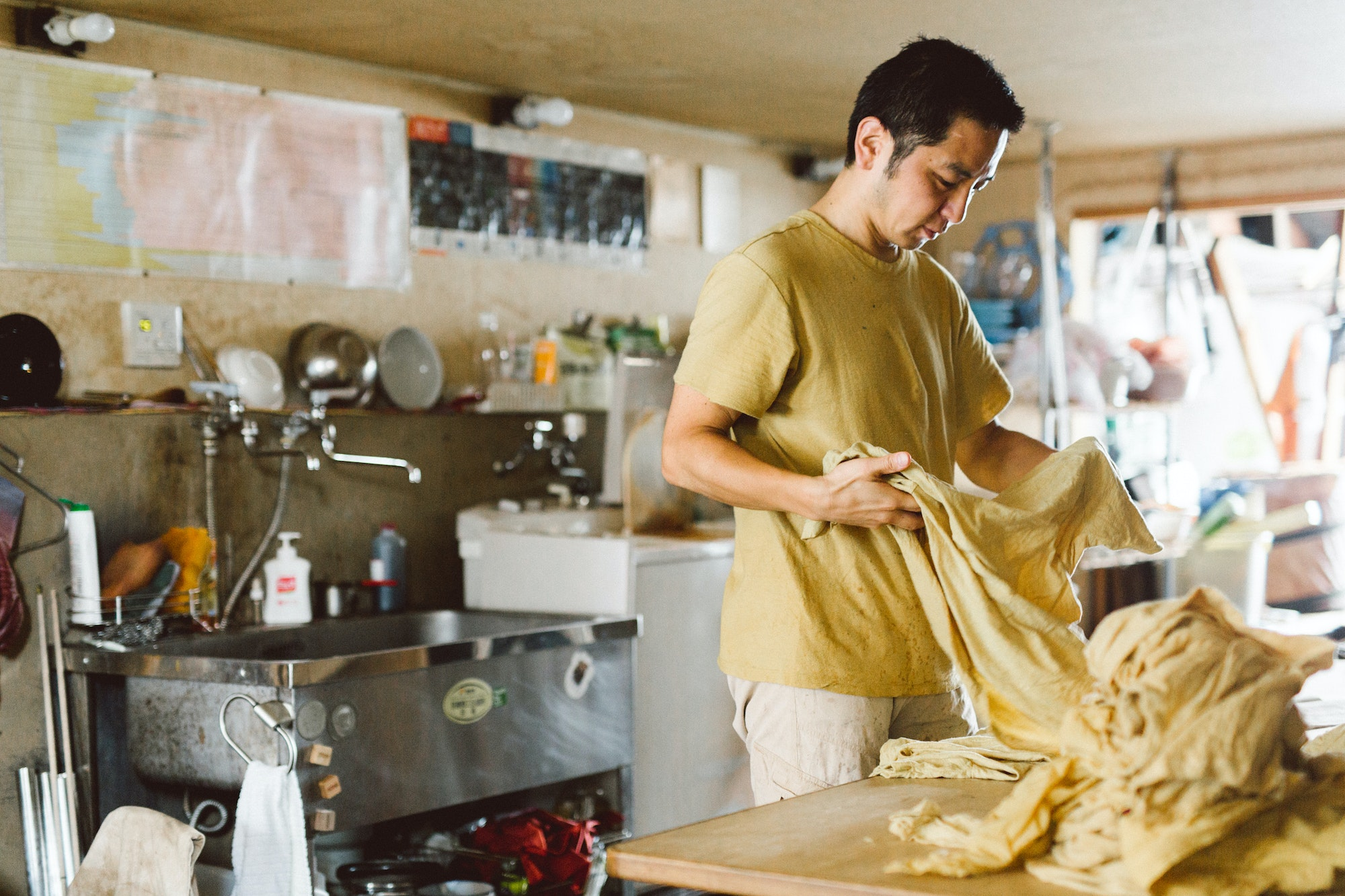 To color Tezomaya's casual cotton apparel, Masaaki Aoki uses dyes made from dried plants and other natural ingredients.