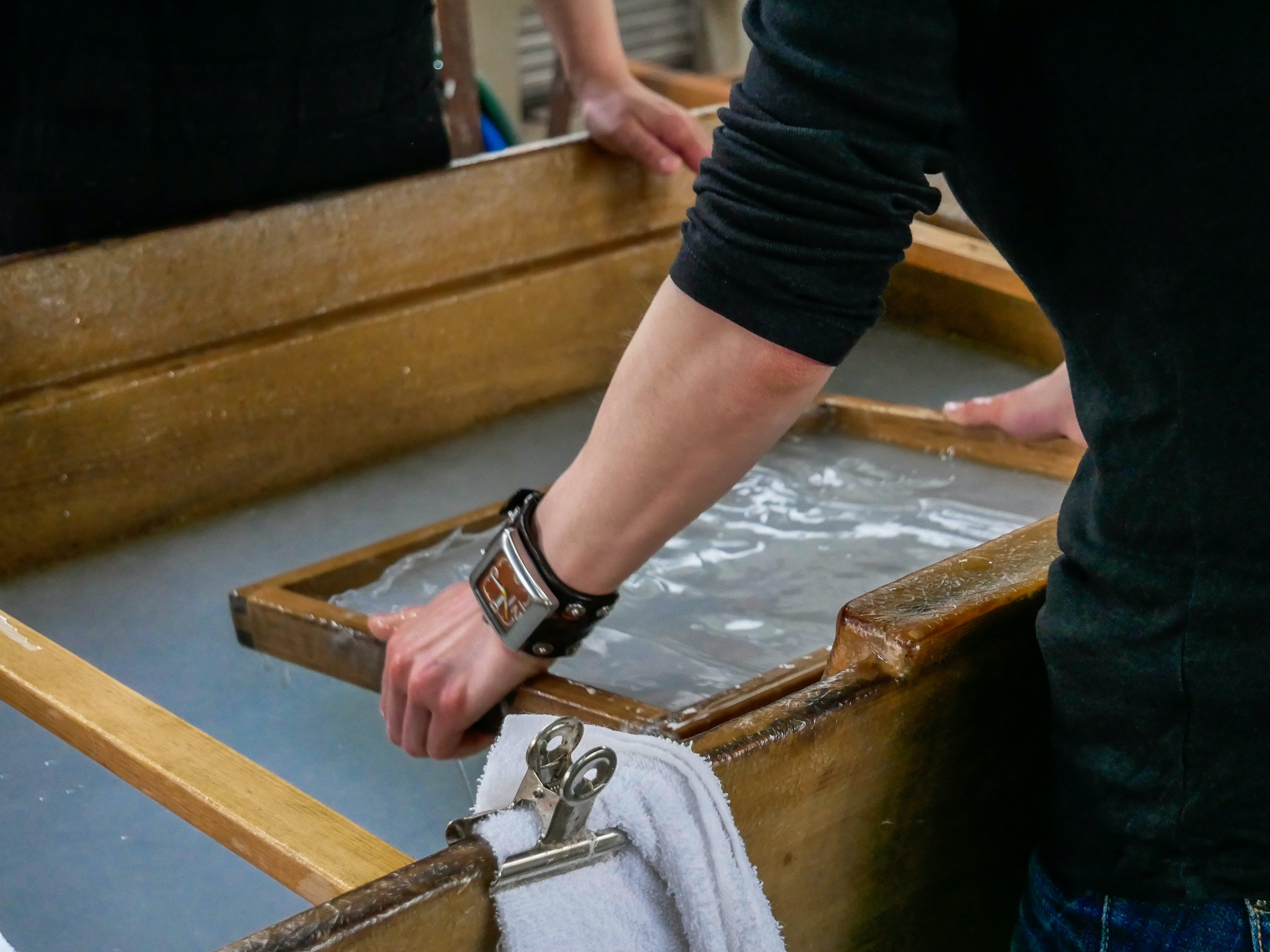 A tourist tries traditional Japanese washi papermaking, a specialty craft of Japan's Goka region.