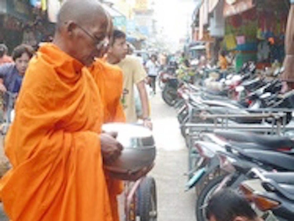 Offering Alms to the Monks at the morning market Bangkok  Thailand