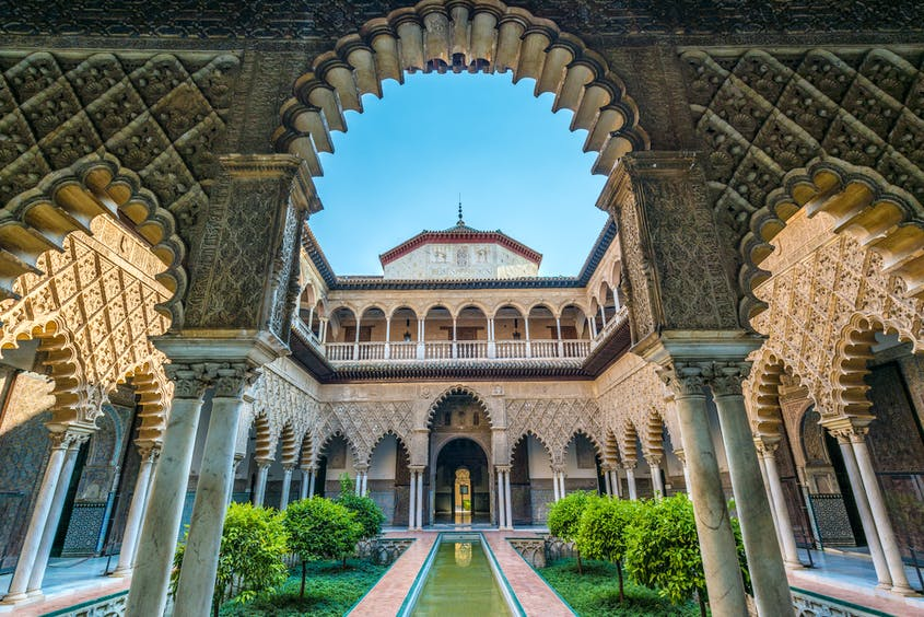 The Alcázar of Seville is fortified palace composed of zones constructed in different historical stages of architecture.