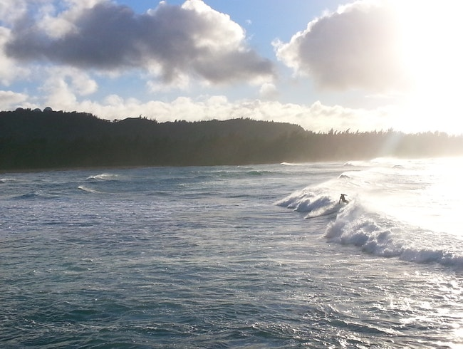 The Sun Breaks Through Afternoon Clouds on Oahu's North Shore, Showing the Surfers Some Love