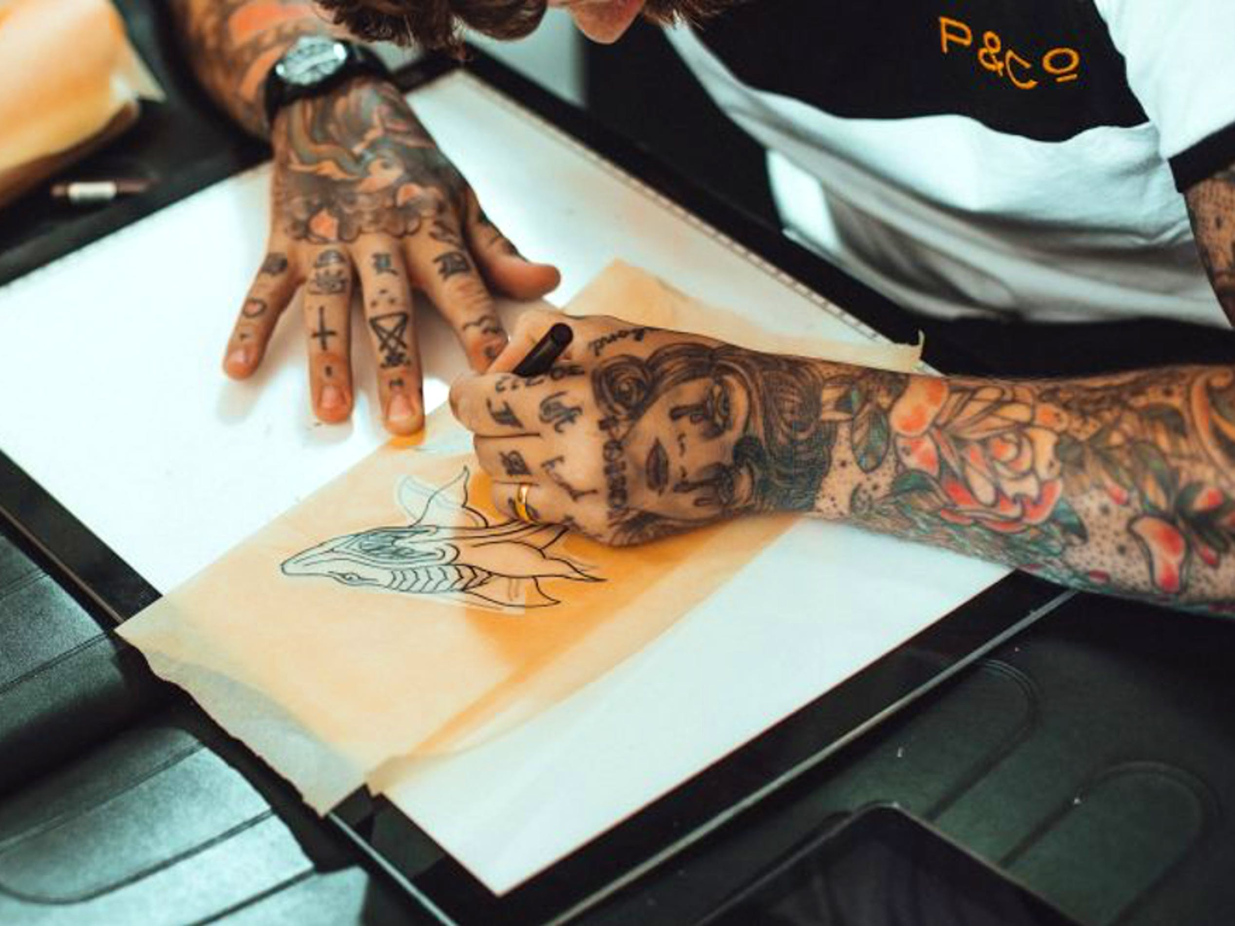 An artist at Vagabond Tattoo in London traces a sketch to produce a temporary stencil that will help him and the client determine where to place the tattoo. Stencils don't depict shading and color the same way a sketch does, so don't hesitate to ask your artist for clarification when deciding if you want to resize or reposition the stencil before the actual tattooing begins.