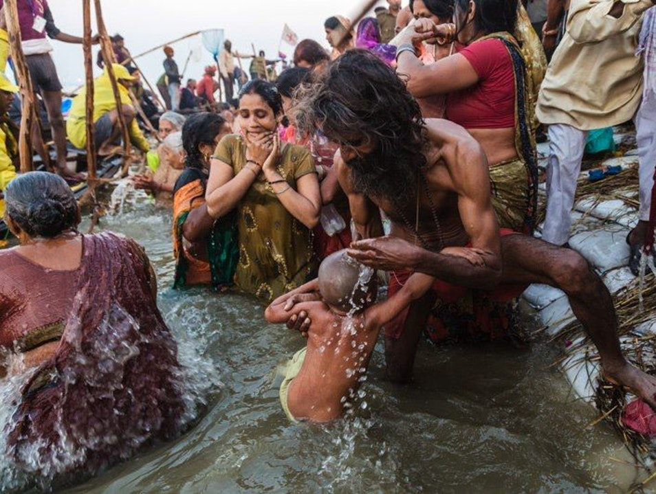 Hindu Man Giving his Son his First Holy Dip in the Ganges