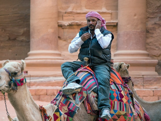 Camel driver on his cell phone
