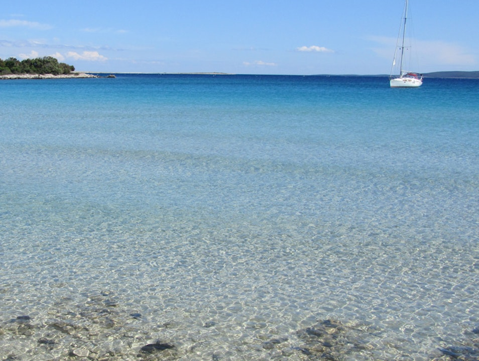 Swimming on empty sandy beach in Croatia Cres  Croatia