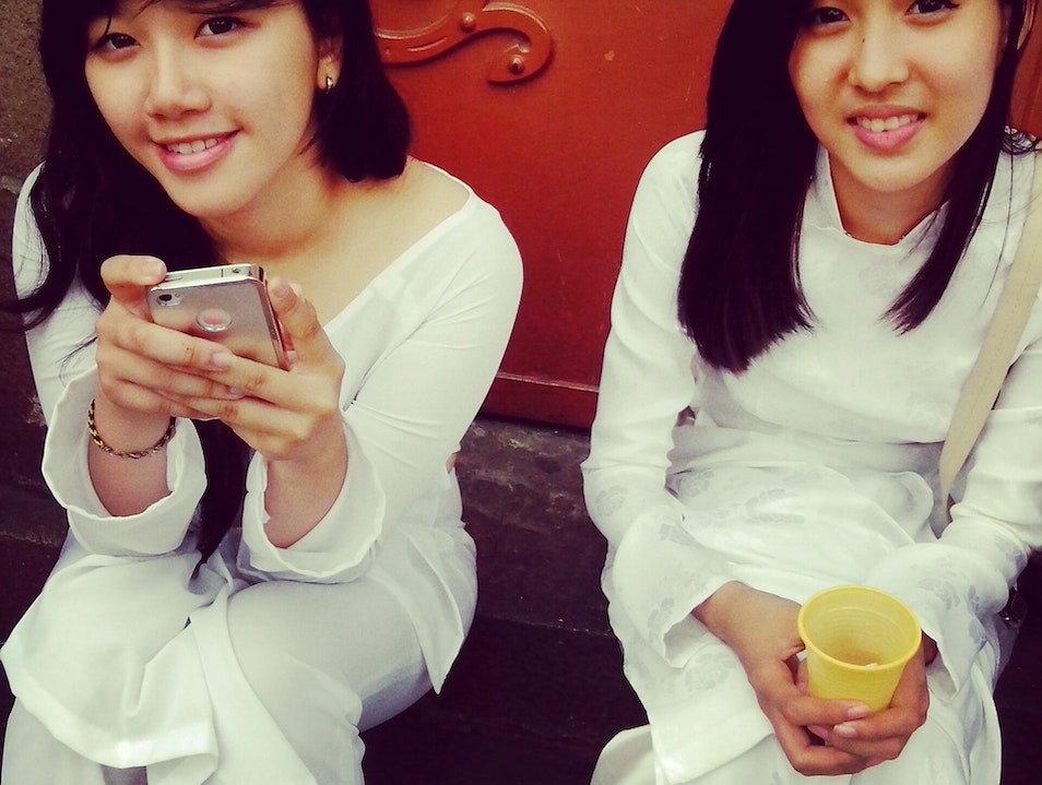 Girls sitting outside Notre Dame Cathedral Ho Chi Minh City  Vietnam