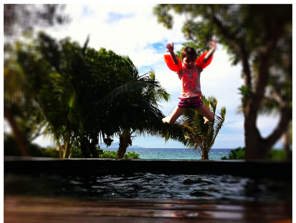 My daughter Sylvie jumping into a pool on Vomo Island.