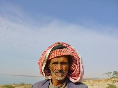 A camel herder walks his camels along the Dead Sea Karak  Jordan