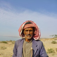 A camel herder walks his camels along the Dead Sea