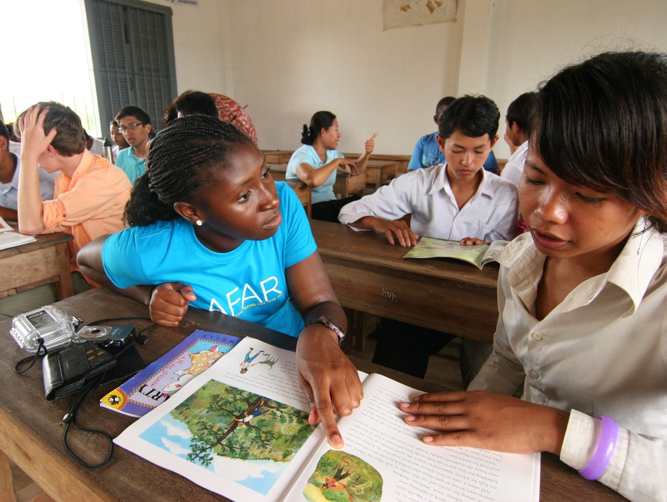 Helping students at Chi Phat secondary school practice reading English Phnom Penh  Cambodia