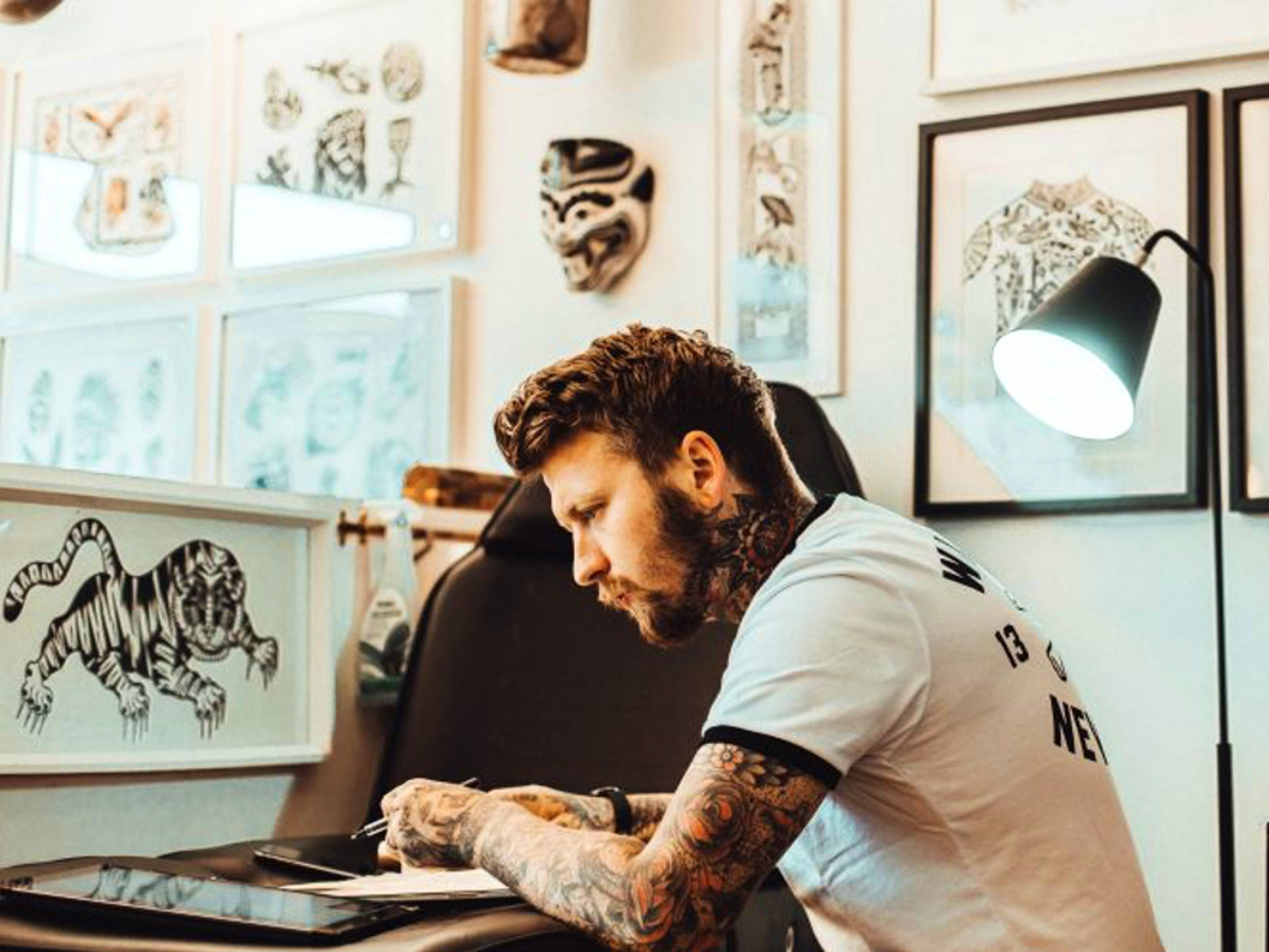Vagabond Tattoo in London has a reputation for extraordinary custom designs. Here, an artist sketches an original piece for a client, checking reference photos along the way.