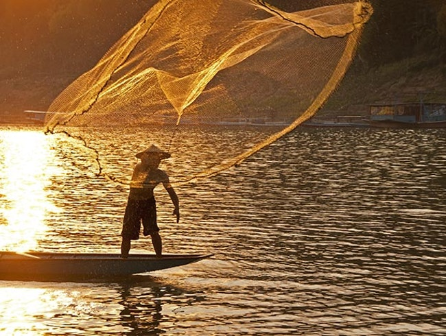 Fisherman tossing net on Mekong River near Luang Prabang, Laos.