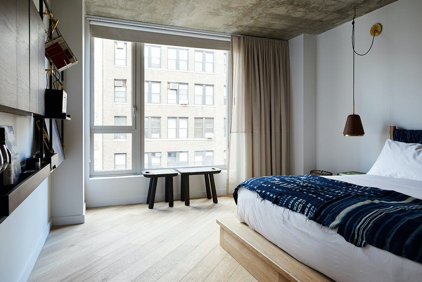 Rooms at Made Hotel include stylish bronze shelves, rich fabrics, and hand-carved benches.