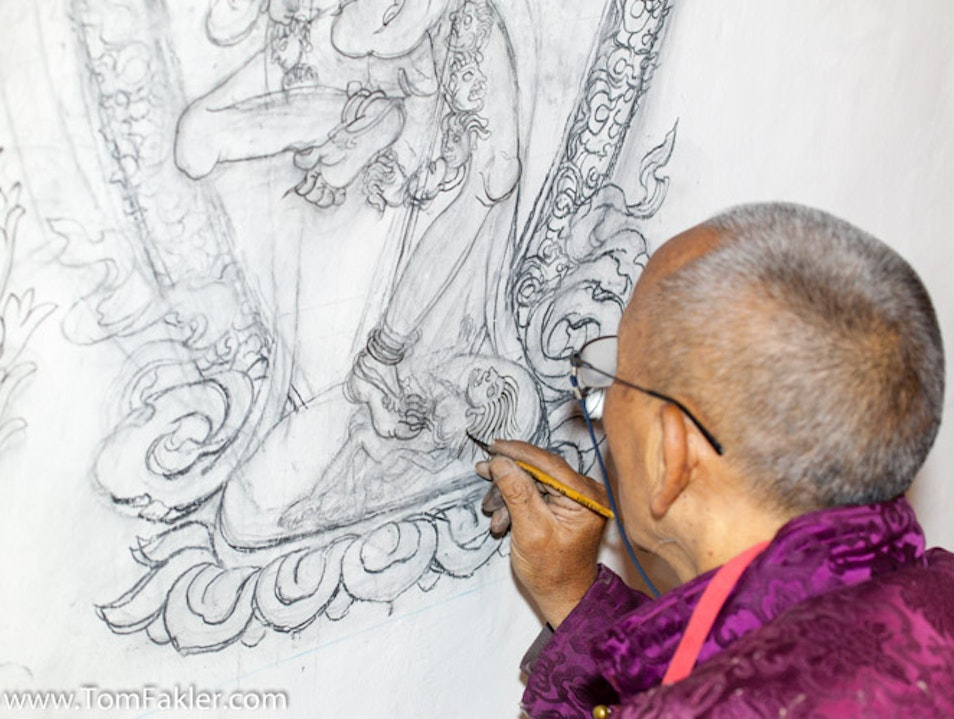 Lama Shashi Dhoj paints over the design he sketched with charcoal. Annapurna Conservation Area  Nepal