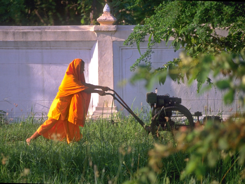 Buddhist Monk and antiquated lawn mower!