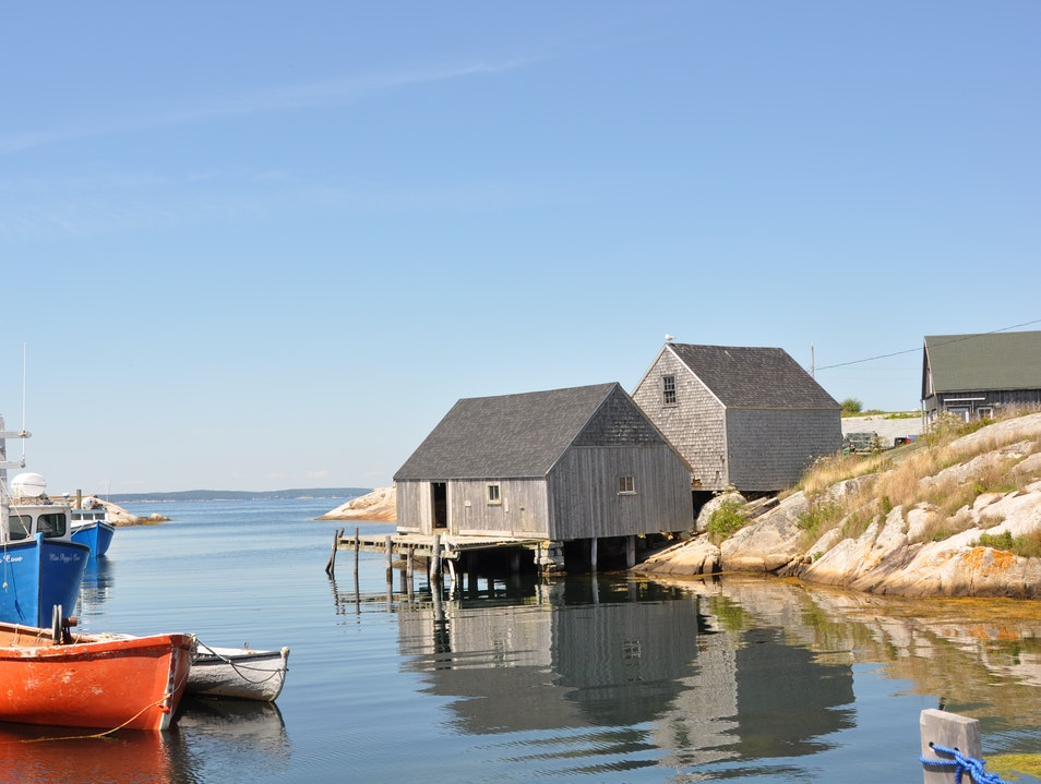 Sea-kayaking into the shelter of Peggy's Cove from the rolling waves in the open ocean.  Peggys Cove  Canada