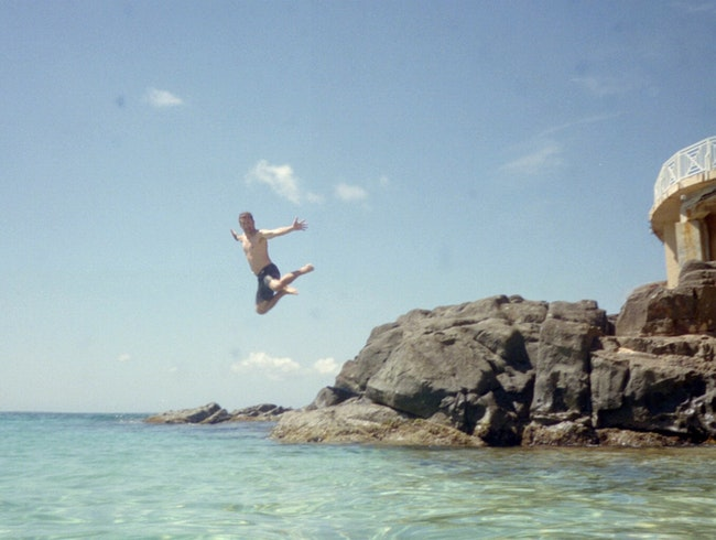 Leaping off the rocks at Baie Rouge