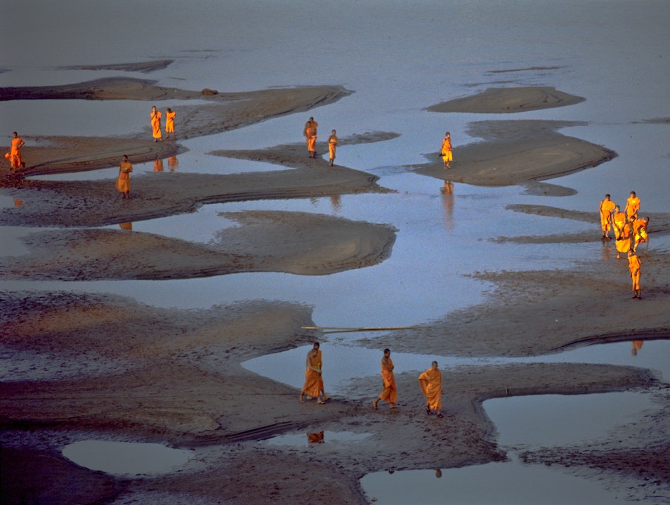 Buddhist Monks take a stroll, Mekong River bed at low water. Phon Sawan  Thailand