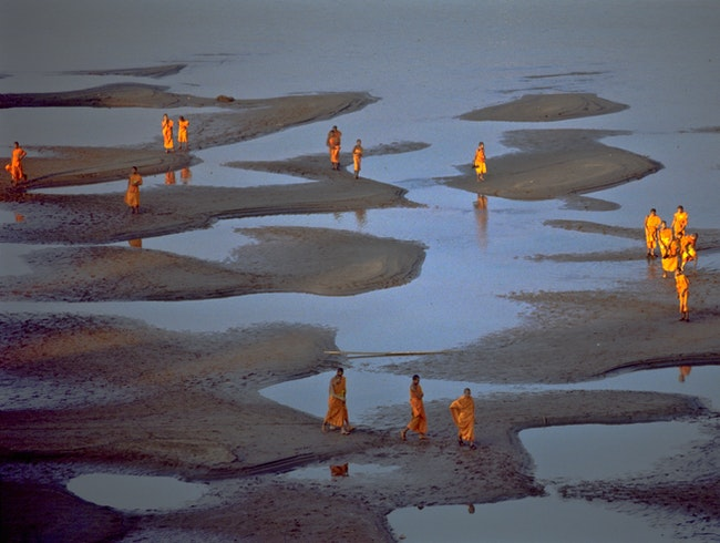 Buddhist Monks take a stroll, Mekong River bed at low water.